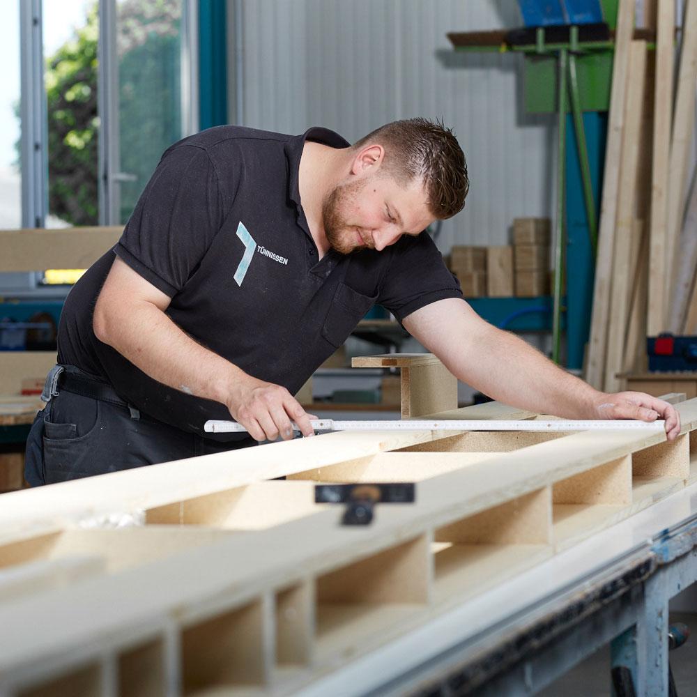Schreinermeister arbeitet am Werkstück - Tünnissen Messen, Corporate Interiors, Events und Ausstellungen
