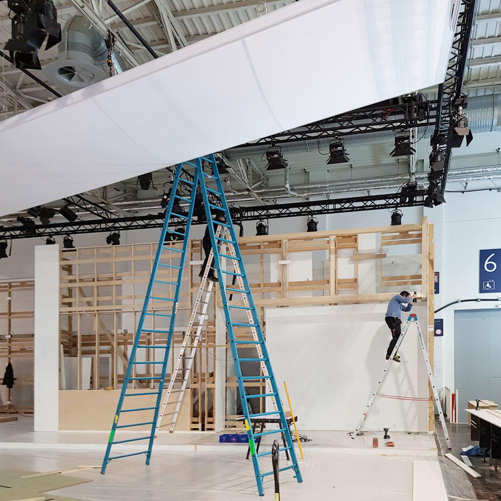 Aufbau der Standarchitektur in einer Messehale mit Monteuren auf Leitern - Tünnissen Interiors, Messen, Events und Ausstellungen NRW Deutschland Europe