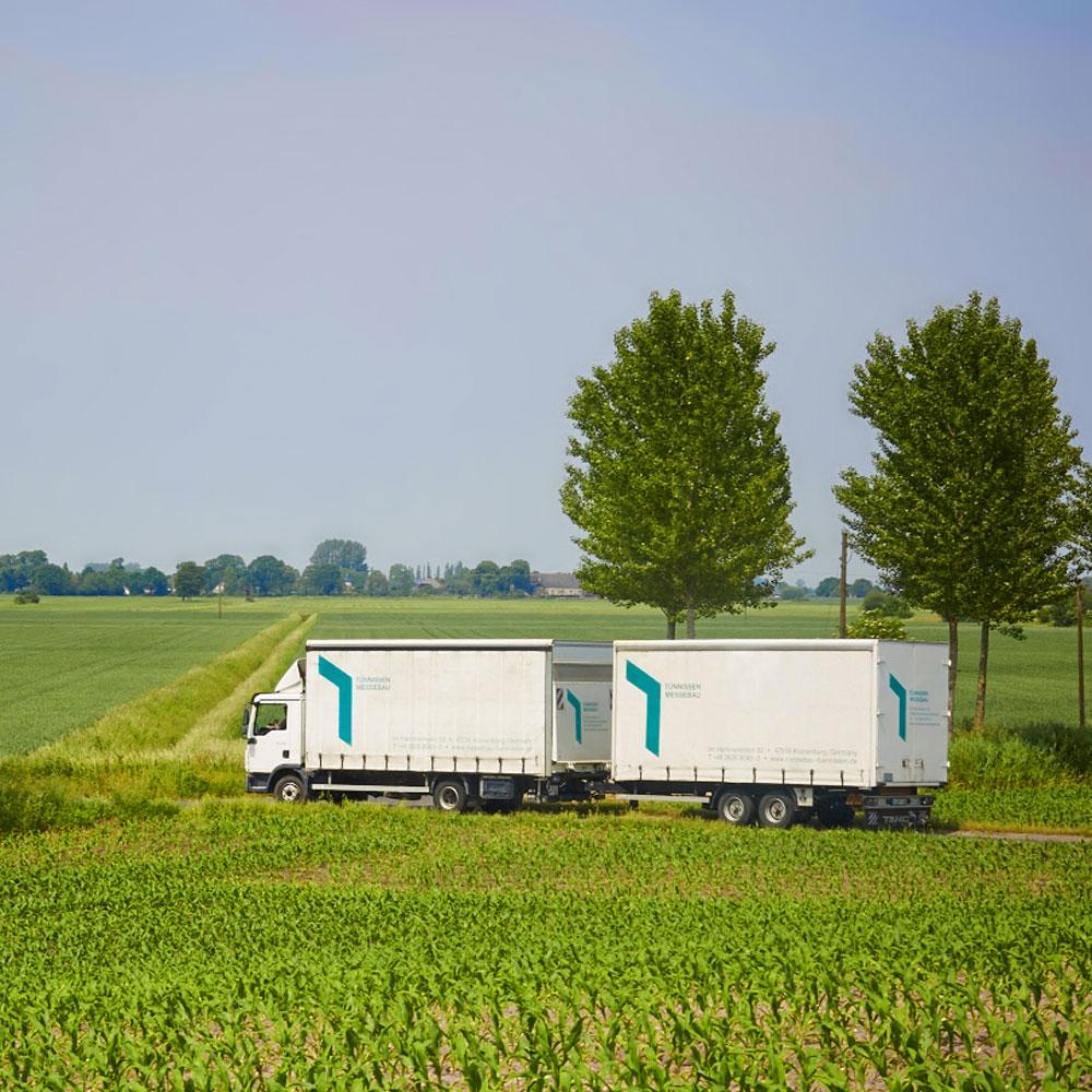 Tünnissen LKW mit Anhänger auf dem Weg durch grüne Landschaft zum Einsatzort - Tünnissen Interiors, Messen, Events und Ausstellungen NRW Deutschland Europe