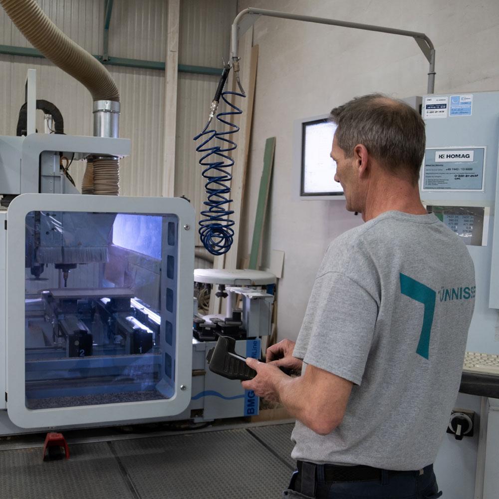 Mitarbeiter steuert die CNC-Fräse in der Produktion - Tünnissen Interiors, Messen, Events und Ausstellungen NRW Deutschland Europe